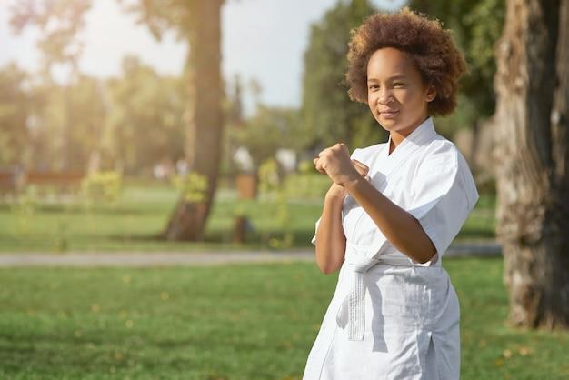 Jolie fille afro-américaine pratiquant les arts martiaux à l'extérieur