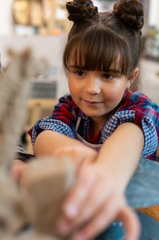 Jolie fille d'âge préscolaire aux yeux sombres se sentant impliquée dans la sculpture de l'argile