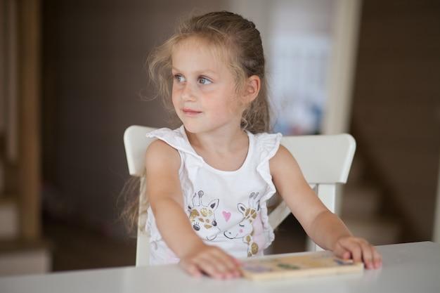 Jolie fille d'âge préscolaire jouant à des jeux éducatifs avec des figures de pâte à modeler se préparant à l'école à la maternelle