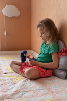 Jolie fille d'âge préscolaire jouant avec une poupée dans la chambre