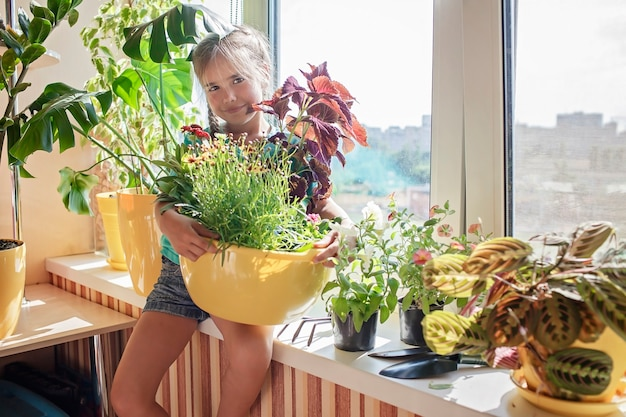 Jolie fille aidant à prendre soin des plantes à la maison sur le concept de parents de plantes de fenêtre de balcon