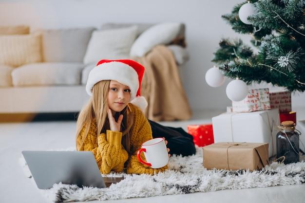 Jolie fille à l'aide d'ordinateur par arbre de noël