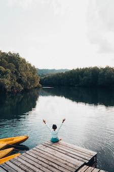 La jolie fille aime le repos naturel et la vue sur la rivière et la mangrove.
