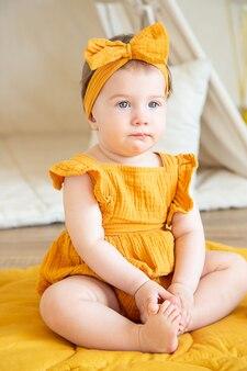 Une jolie fille d'un an en vêtements jaunes est assise sur le sol et regarde ailleurs