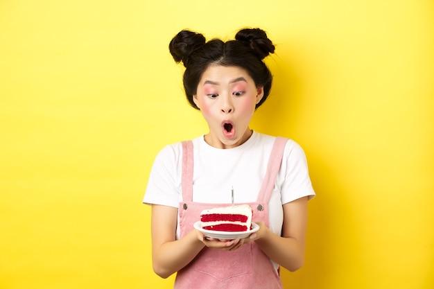 Jolie fille d'anniversaire asiatique avec un maquillage lumineux, soufflant une bougie sur un gâteau, faisant un souhait, debout sur le jaune