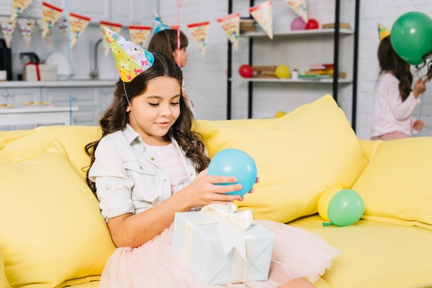 Jolie fille d'anniversaire assise sur le canapé tenant un ballon dans la main en regardant une boîte cadeau