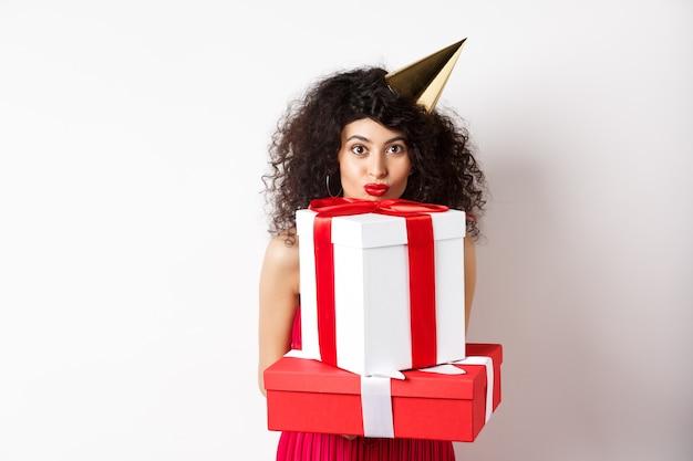 Jolie fille d'anniversaire aux cheveux bouclés et chapeau de fête, tenant des cadeaux et regardant heureux à la caméra, debout sur fond blanc.