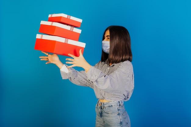 Jolie fille d'anniversaire dans un masque médical, jette des coffrets cadeaux.