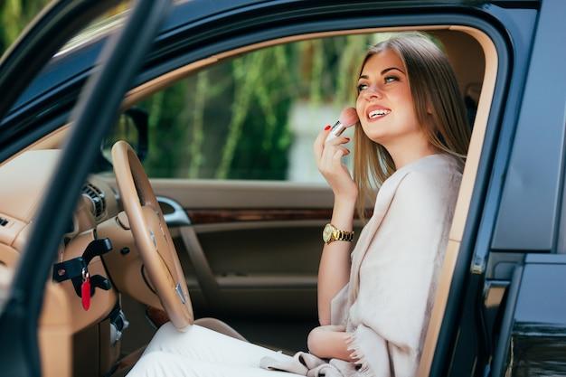 Jolie fille appliquant le rouge à lèvres dans une voiture