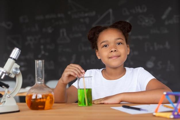 Jolie fille en apprenant plus sur la chimie en classe