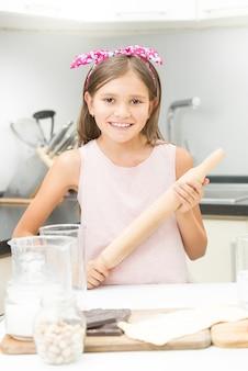 Jolie fille avec un arc rose sur les cheveux posant avec un rouleau à pâtisserie en bois