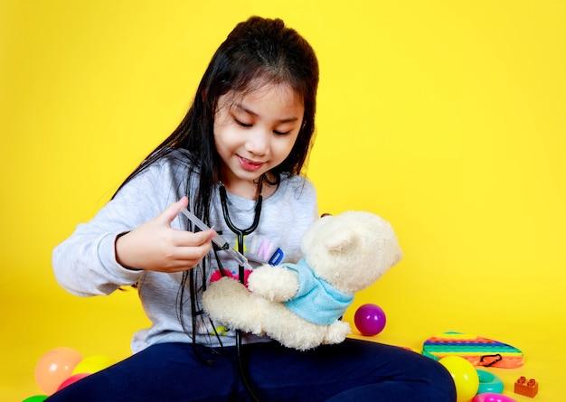 Une jolie fille asiatique aime jouer avec une balle colorée et une seringue en injectant un médicament amusant dans une petite poupée ours bien-aimée. exerçant en tant que docteur en pharmacie empathique heureux de guérir la maladie d'un jouet pour enfant animal