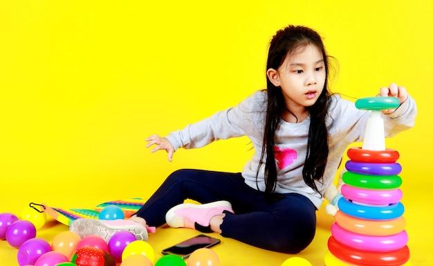 Une jolie fille asiatique aime s'entraîner à insérer un cerceau en plastique coloré dans un cône triangulaire pour en savoir plus sur la séquence de taille, la pile de couches et la forme tout en étant assise sur un enfant jouant au sol avec une balle et un jouet amusants