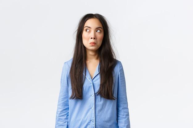 Jolie fille asiatique confuse et perplexe aux cheveux en désordre, vêtue d'un pyjama bleu, se réveillant le matin, l'air interrogée dans le coin supérieur gauche, dormi trop longtemps, debout sur fond blanc désemparé