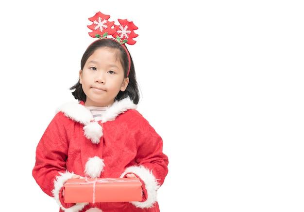 Jolie fille asiatique en costume de père noël tenant la boîte-cadeau et sourire isolé sur fond blanc, christm