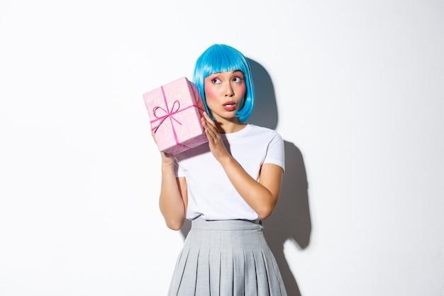 Jolie fille asiatique dans une boîte de tremblement de perruque bleue avec un cadeau, me demande ce qui est à l'intérieur, debout.