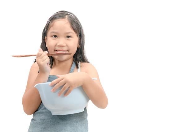 Jolie fille asiatique détenant des ustensiles de cuisine