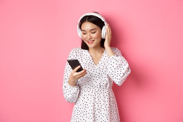 Jolie fille asiatique écoutant de la musique sur des écouteurs, regardant un téléphone portable et souriant, debout en robe sur fond rose