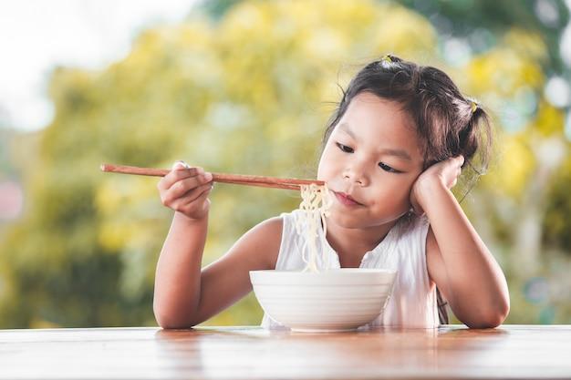 Jolie fille asiatique enfant s'ennuie à manger nouilles instantanées pour son repas