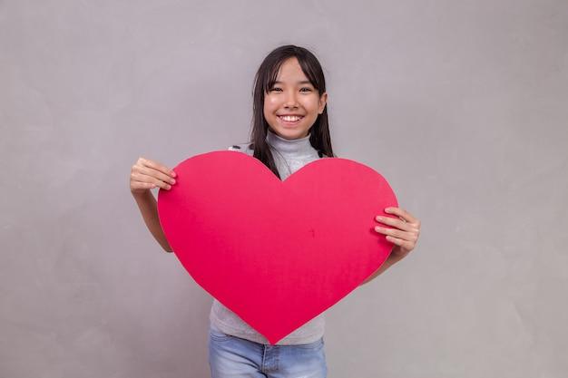 Jolie fille asiatique avec une énorme carte de coeur avec un espace pour le texte.