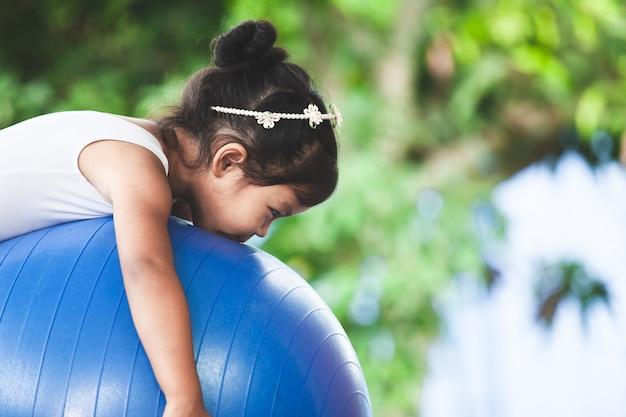 Jolie fille asiatique faisant de l'exercice d'étirement sur le ballon de fitness