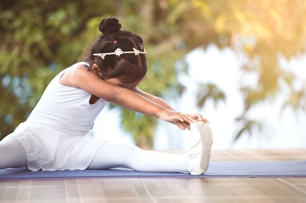 Jolie fille asiatique faisant des exercices d'étirement et pratiquant un ballet