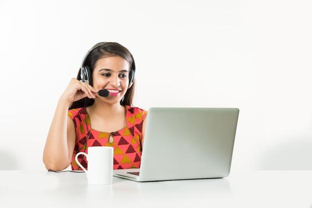 Jolie fille asiatique indienne ou employé de bpo ou de centre d'appels parlant au casque avec un ordinateur portable sur la table