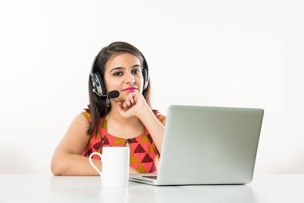 Jolie Fille Asiatique Indienne Ou Employé De Bpo Ou De Centre D'appels Parlant Au Casque Avec Un Ordinateur Portable Sur La Table Photo Premium