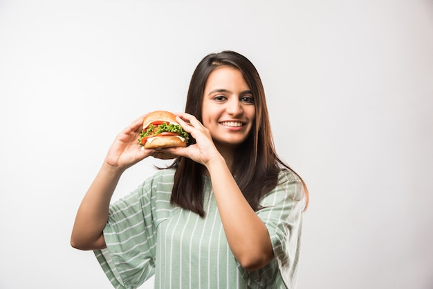 Jolie fille asiatique indienne mangeant un hamburger sur fond blanc ou jaune