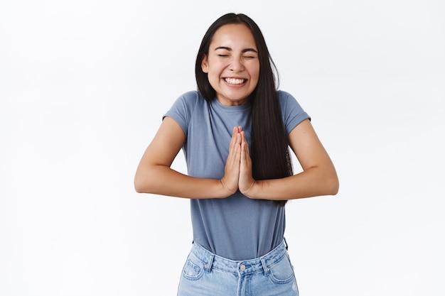 Une jolie fille asiatique joyeuse et excitée croit que les rêves se réalisent, prient ou triomphent, serrent les mains ensemble dans la prière, le mouvement de supplication, ferme les yeux et sourit largement, réussit, souhaite exaucé