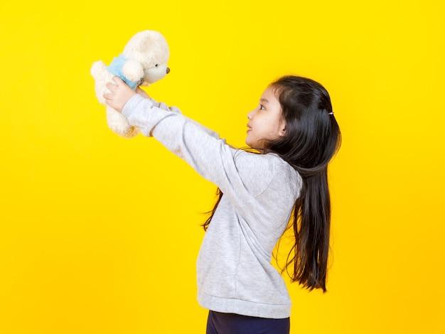 Jolie fille asiatique liitlw tenant et jouant avec une poupée nue en peluche sur fond jaune. concept d'enfant drôle et imagination.