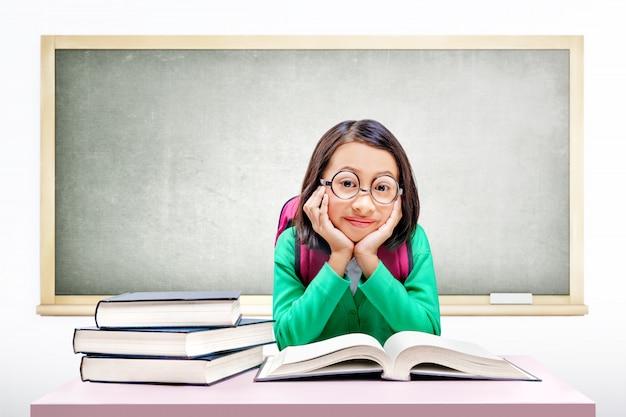 Jolie fille asiatique avec des lunettes et sac à dos avec des livres sur le bureau