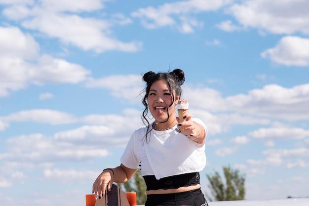 Jolie fille asiatique, manger des glaces dans le parc, des vêtements décontractés et de la planche à roulettes