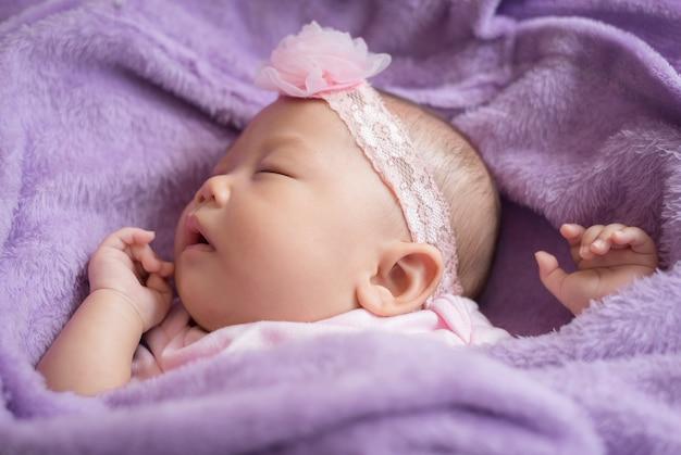 Jolie fille asiatique nouveau-née dormant sur un tissu à fourrure portant un bandeau de fleur rose.