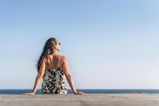 Jolie fille asiatique pan en robe assis sur le quai près de la mer.