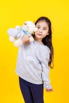 Jolie fille asiatique portant un pull, prenant une photo de portrait étreignant une belle poupée d'ours sur fond jaune.