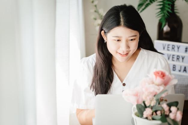 Une jolie fille asiatique souriante dans la maison pour une jeune femme au foyer asiatique heureuse de profiter du style de vie à la maison.