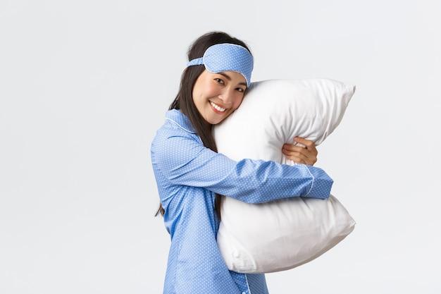Jolie fille asiatique souriante avec une peau propre, portant un masque de sommeil et un pyjama prêt pour le coucher