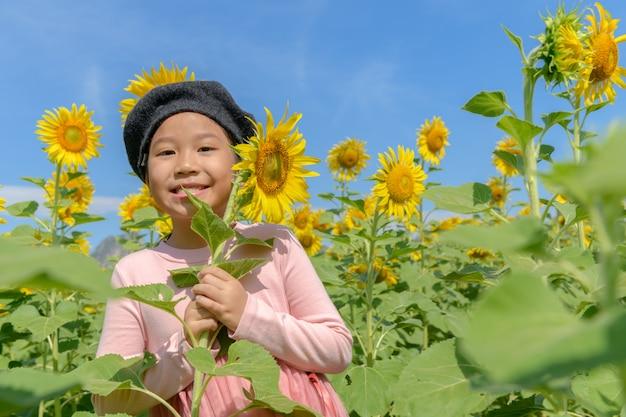Jolie fille asiatique sourire avec fleur de tournesol
