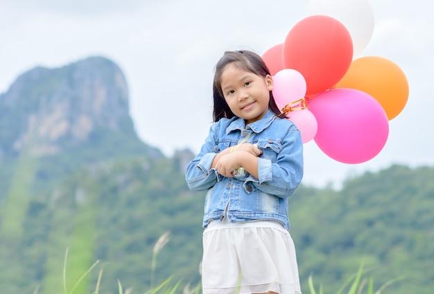 Jolie fille asiatique sourire et tenant le ballon,