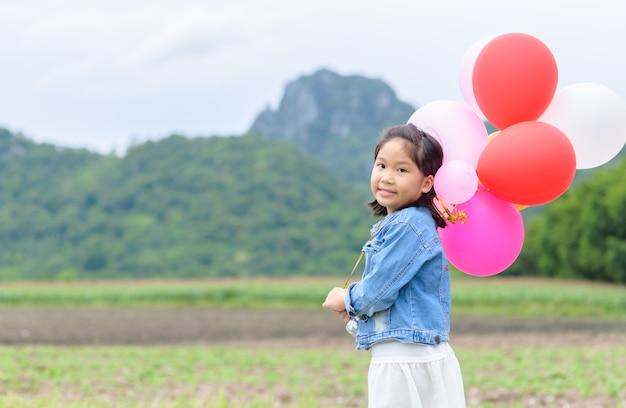 Jolie fille asiatique sourire et tenant le ballon