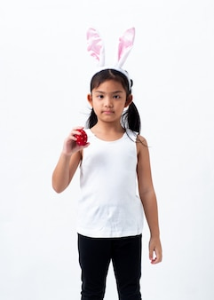 Une jolie fille asiatique tenant un oeuf de pâques