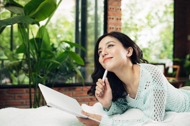 Jolie fille asiatique travaillant sur son projet scolaire à la maison