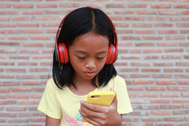Une jolie fille asiatique utilise un casque sans fil rouge pour écouter de la musique sur son téléphone