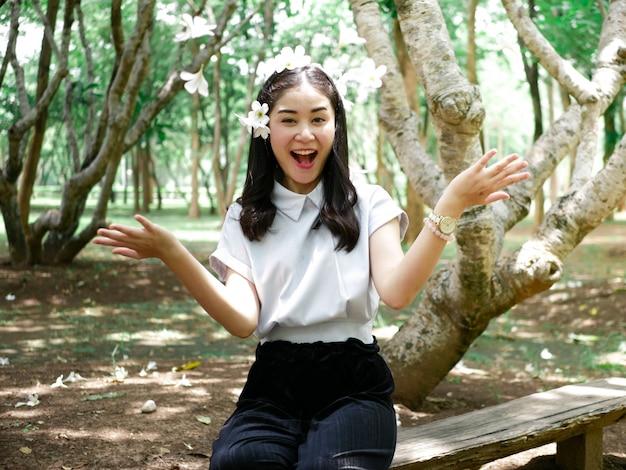Jolie fille asiatique en voyage nature en plein air. elle sourit et pose avec fleur dans beaucoup d'instant.
