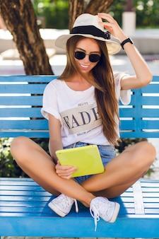 Jolie fille assise sur un banc bleu et jouant sur une tablette dans un étui jaune.