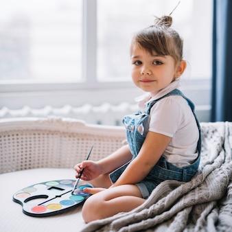 Jolie fille assise sur un canapé avec une palette d'aquarelle