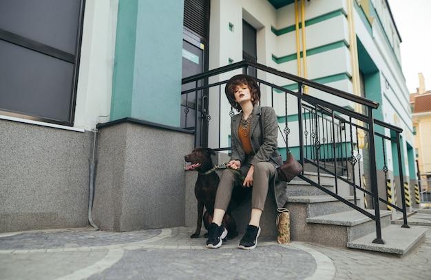 Jolie fille assise avec un chien dans les escaliers près du bâtiment et se penche sur la caméra
