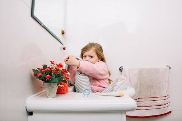 Jolie fille assise dans le lavabo de la salle de bain