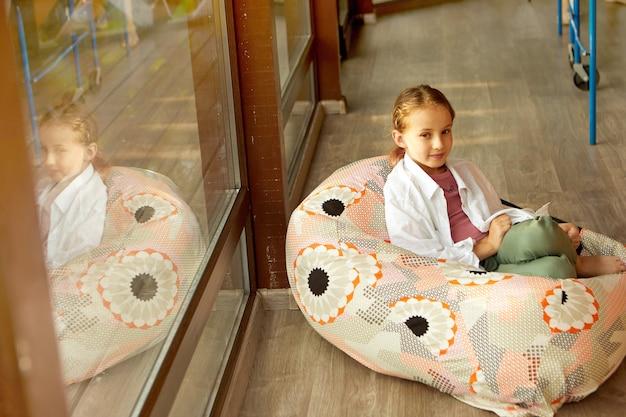 Jolie fille assise dans un sac de haricots près de la fenêtre
